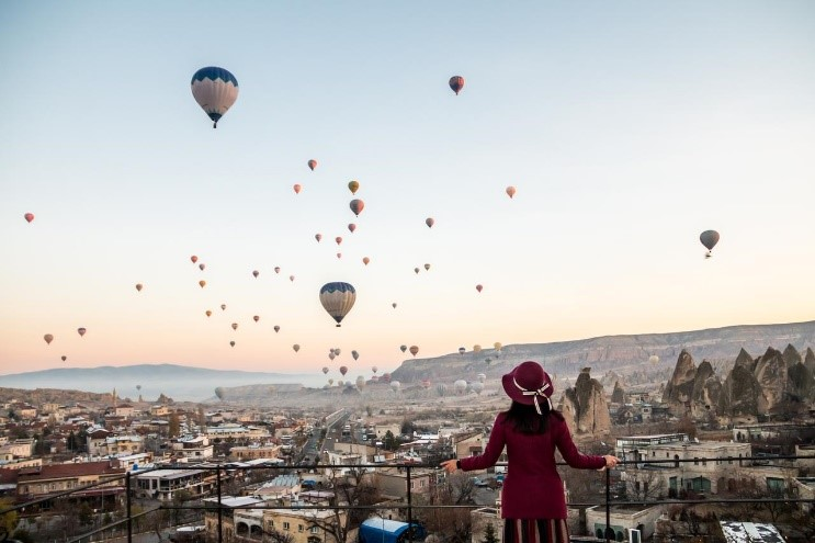 Woman watching hot air balloons on the horizon