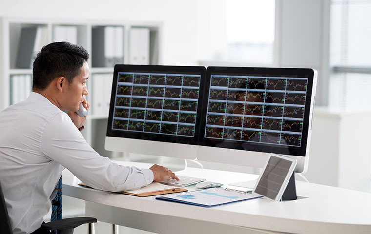 A colleague talking on phone and looking at multiple trade dashboard on computer screens
